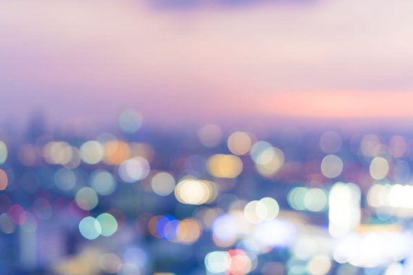 Ville au coucher de soleil avec des points lumineux flous